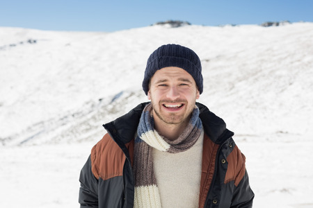 Portrait of a smiling young man in warm clothing standing on snow covered landscape