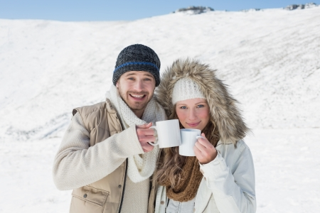 Portrait of a cheerful young couple in warm clothing with coffee cups on snow covered landscape photo