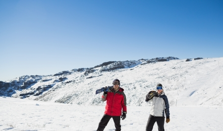 ski walking: Full length of a couple carrying ski boards while walking on snow covered landscape