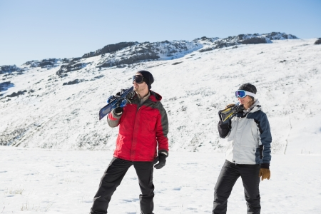 ski walking: Smiling couple carrying ski boards on shoulders while walking on snow covered landscape Stock Photo