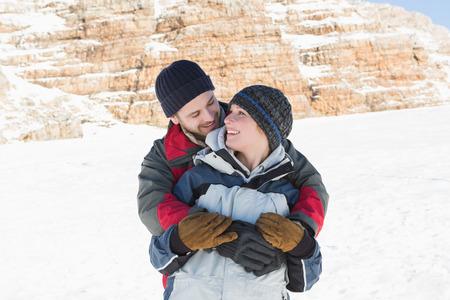 mujer de espaldas: Hombre feliz abrazando mujer de espaldas sobre la nieve cubre el paisaje