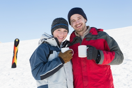 Happy loving couple having coffee with ski board on snow in background against clear blue sky photo