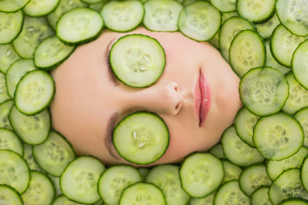 beauty salon face: Close up of a young beautiful woman with facial mask of cucumber slices on her face at spa salon Stock Photo