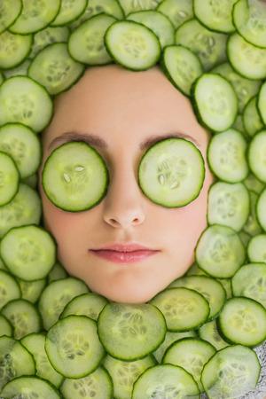 tratamiento facial: Primer plano de una joven y bella mujer con máscara facial de rodajas de pepino en la cara en el salón de spa