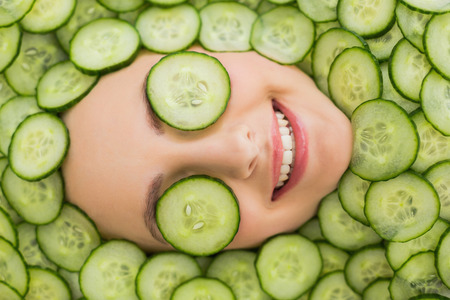 Close up of a young beautiful woman with facial mask of cucumber slices on her face at spa salon Фото со стока