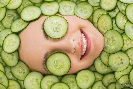 Close-up van een jonge mooie vrouw met gezichtsmasker van plakjes komkommer op haar gezicht in de spa salon