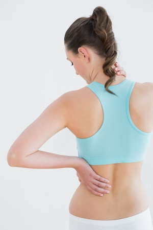 fits in: Rear view of a toned young woman with back pain standing against wall in fitness studio Stock Photo