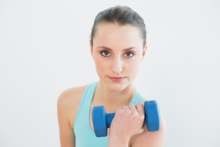 Portrait of young woman with dumbbell against wall at fitness studio photo