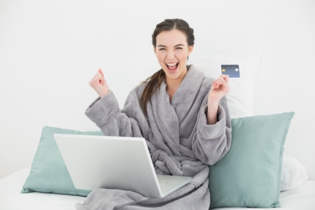 Excited young woman in bathrobe doing online shopping through laptop and credit card in bed photo
