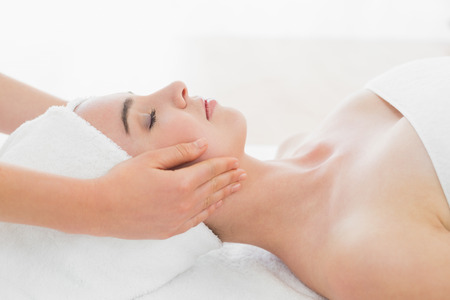 Side view of hands massaging a beautiful womans face at beauty spa