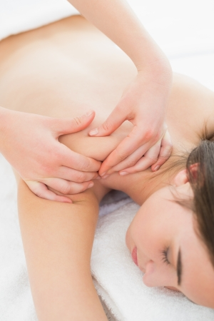 Close up of a beautiful woman enjoying shoulder massage at beauty spa photo