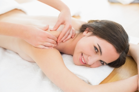 Portrait of a smiling beautiful woman enjoying shoulder massage at beauty spa
