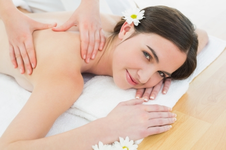 therapy room: Close up of a beautiful woman enjoying back massage at beauty spa