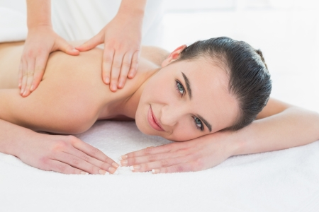 Close up of a beautiful woman enjoying back massage at beauty spa photo