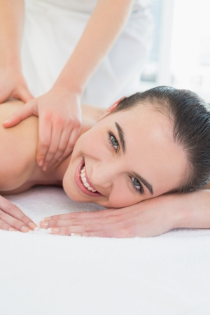 therapy room: Close up of a beautiful woman enjoying shoulder massage at beauty spa
