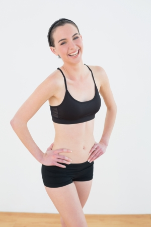 Portrait of a smiling toned young woman with hands on hips in fitness studio photo