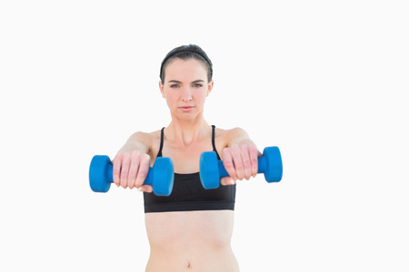 Portrait of a serious young woman with dumbbells against white background photo