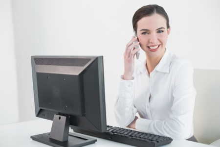 Portrait of a smiling young businesswoman using mobile phone in front of computer in office photo
