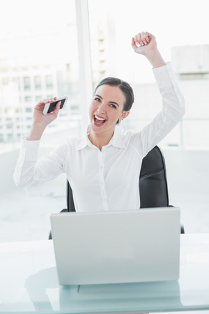 Cheerful elegant businesswoman cheering with hands raised at office desk photo