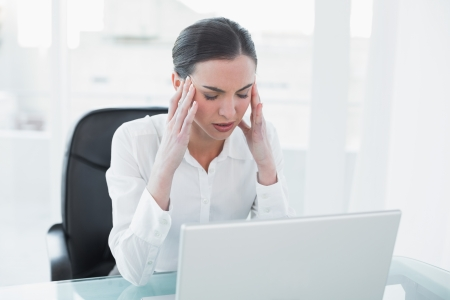Young businesswoman suffering from headache in front of laptop at office desk