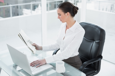 Concentrated businesswoman reading newspaper while using laptop at desk in a bright office photo