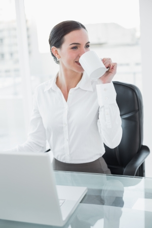 Smiling businesswoman drinking coffee while using laptop at desk in a bright office photo