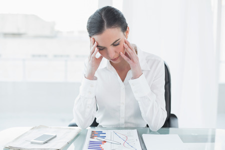 tied down: Worried young businesswoman with graphs sitting at office desk Stock Photo