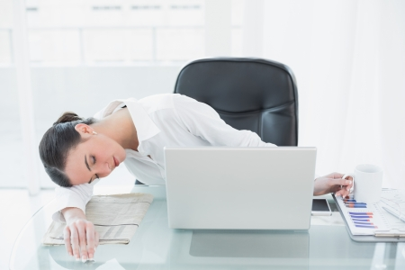 Tired young businesswoman resting at desk in a bright office photo