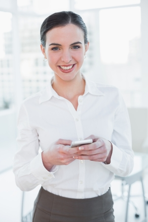 Portrait of an elegant young businesswoman with mobile phone in a bright office photo