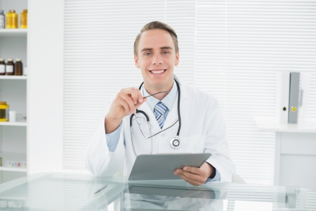 Portrait of a smiling male doctor with digital tablet at medical office photo
