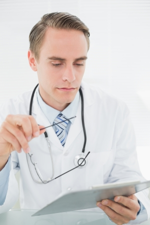 Serious male doctor looking at digital tablet at medical office photo