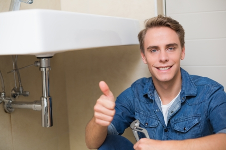 Portrait of a handsome plumber gesturing thumbs up besides washbasin in bathroom photo