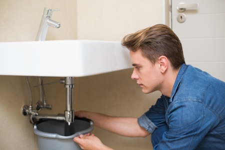 Side view of a handsome plumber repairing the drain of sink in bathroom