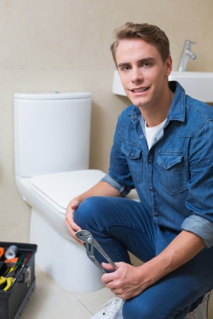 Portrait of a smiling handsome plumber with toolbox doing toilet reparation photo