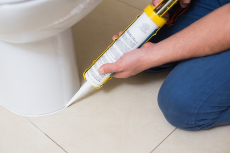 Close up of a plumber fixing toilet in a washroom with silicone cartridge Reklamní fotografie - 25461443