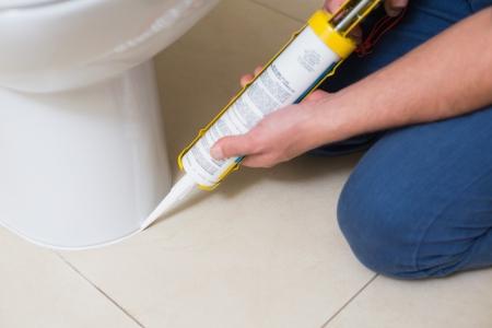 Nahaufnahme von einem Klempner, die Festsetzung Toilette in einem Waschraum mit Silikon-Patrone
