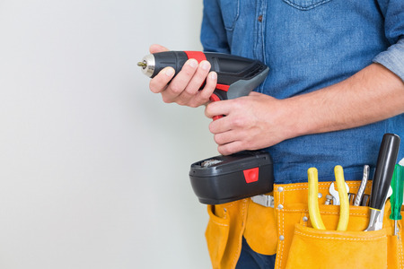 toolbelt: Close up mid section of a handyman with drill and toolbelt by the wall