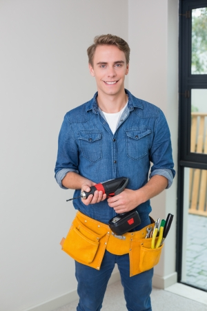 toolbelt: Portrait of a handsome young handyman holding a drill with toolbelt around waist Stock Photo
