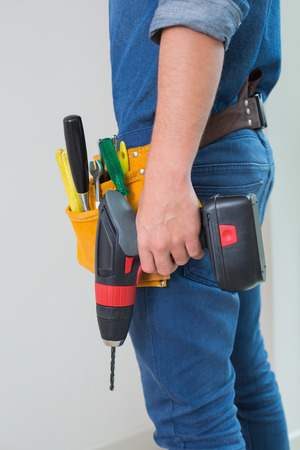 toolbelt: Side view mid section of a handyman with drill and toolbelt by the wall Stock Photo