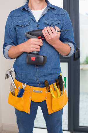 toolbelt: Close up mid section of a handyman with drill and toolbelt Stock Photo