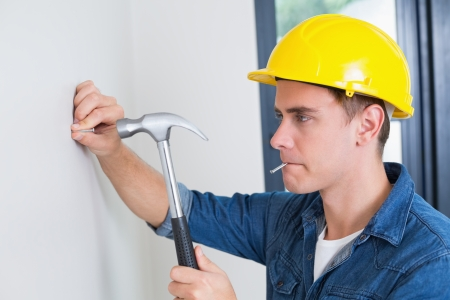 hammering: Close up of a serious young handyman hammering nail in wall
