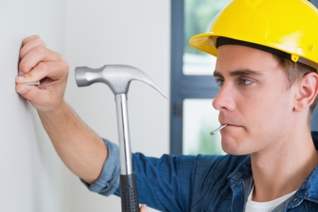 Close up of a serious young handyman hammering nail in wall photo