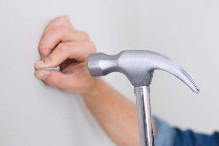 Extreme Close up of a handyman hammering nail in wall photo
