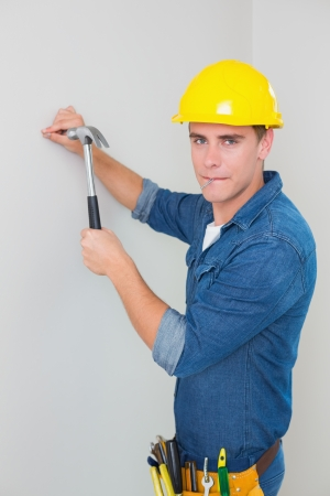Portrait of a young handyman hammering nail in wall photo