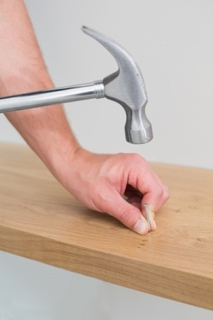 Extreme Close up of a handyman hammering nail in wooden bench photo