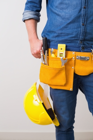 toolbelt: Mid section of a handyman with toolbelt around his waist and hard hat