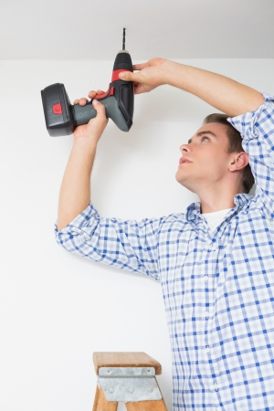 Low angle view of a young handyman using a cordless drill to the ceiling photo