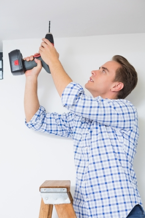Side view of a young handyman using a cordless drill to the ceiling photo