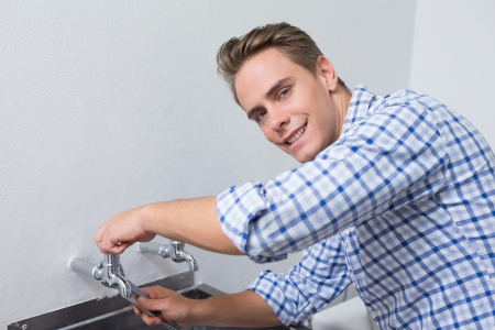 Portrait of a smiling plumber fixing water tap with pliers photo