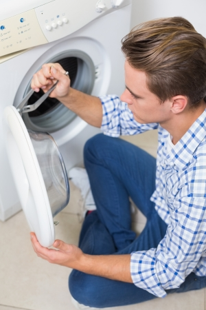 Side view of a technician repairing a washing machine photo